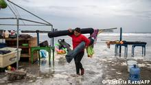 A woman removes umbrellas from the beach as strong waves reach the coast due to Hurricane Grace, which has reached category 2, in Boca del Rio, Veracruz, Mexico, on August 20, 2021. - Grace regained hurricane strength Friday as it barreled towards Mexico for a second time, triggering warnings of flooding and mudslides in mountains on the eastern mainland. (Photo by VICTORIA RAZO / AFP)