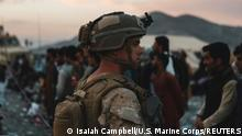 A Marine assigned to Special Purpose Marine Air Ground Task Force-Crisis Response-Central Command assists evacuees during an evacuation at Hamid Karzai International Airport, in Kabul, Afghanistan, August 20, 2021. Sgt. Isaiah Campbell/U.S. Marine Corps/Handout via REUTERS THIS IMAGE HAS BEEN SUPPLIED BY A THIRD PARTY
