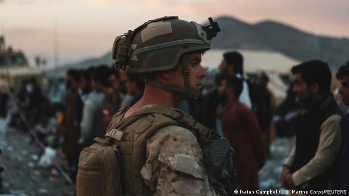 A US soldier assists evacuees during an evacuation at the Kabul airport