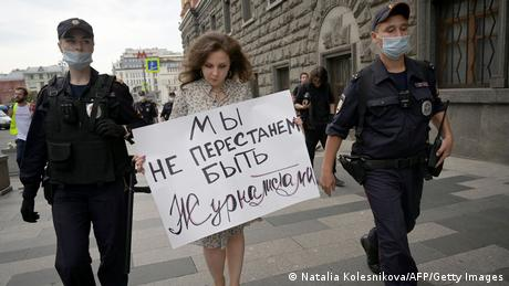 Police officers detain a journalist who holds a placard which reads, We don't stop being journalists