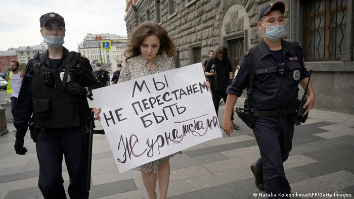 Police officers detain a journalist who holds a placard which reads We don't stop being journalists during a demonstration in Moscow