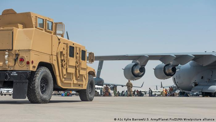 Evacuees from Kabul wait under the wing of a U.S. Air Force C-17 Globemaster lll aircraft after arriving for processing