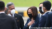 US Vice President Kamala Harris (3rd R) is greeted by Singapore Foreign Minister Vivian Balakrishnan (C) upon her arrival at Paya Lebar Base airport in Singapore on August 22, 2021. (Photo by Roslan Rahman / AFP)