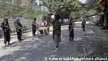22.08.2021, Afghanistan, Kabul: Taliban-Kämpfer stehen an einem Kontrollpunkt im Viertel Wazir Akbar Khan in afghanischen Hauptstadt Kabul und sprechen mit einem Rollerfahrer. In Kabul sind im Gedränge rund um den Flughafen nach Angaben der britischen Regierung sieben Menschen ums Leben gekommen. Foto: Rahmat Gul/AP/dpa +++ dpa-Bildfunk +++