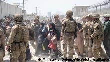 HANDOUT - 21.08.2021, Afghanistan, Kabul: Auf diesem vom Verteidigungsministerium zur Verfügung gestellten Foto beteiligen sich Angehörige des britischen und des US-amerikanischen Militärs an der Evakuierung von Menschen aus Kabul. Foto: Uncredited/Ministry of Defence/dpa - ACHTUNG: Nur zur redaktionellen Verwendung im Zusammenhang mit der aktuellen Berichterstattung und nur mit vollständiger Nennung des vorstehenden Credits +++ dpa-Bildfunk +++