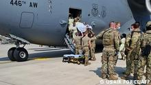 In this image courtesy of the US Air Force, medical support personnel from the 86thMedical Group help an Afghan mother and family off a US Air Force C-17, call sign Reach 828, moments after she delivered a child aboard the aircraft upon landing at Ramstein Air Base, Germany, August 21, 2021. - During an evacuation flight from an Intermediate Staging Base in the Middle East, the mother went into labor and began experiencing complications due to low blood pressure. The aircraft commander made the decision to descend in altitude to increase air pressure in the aircraft, which helped stabilize and save the mother's life. Upon landing, Airmen from the 86thMDG came aboard and delivered the child in the cargo bay of the aircraft. The baby girl and mother were transported to a nearby medical facility and are in good condition. (Photo by - / US AIR FORCE / AFP) / RESTRICTED TO EDITORIAL USE - MANDATORY CREDIT AFP PHOTO / US AIR FORCE - NO MARKETING - NO ADVERTISING CAMPAIGNS - DISTRIBUTED AS A SERVICE TO CLIENTS