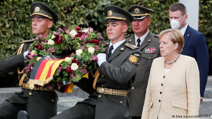 Angela Merkel dan tentara membawa karangan bunga untuk para korban invasi Jerman ke Ukraina selama perang dunia kedua