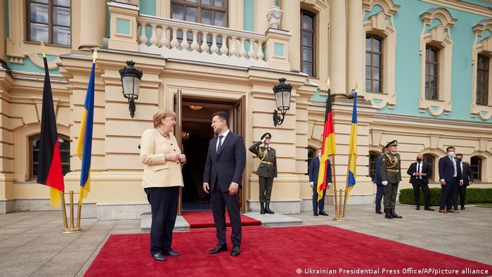 Angela Merkel dan Volodymyr Zelenskyy berdiri di luar gedung pemerintah di Kyiv