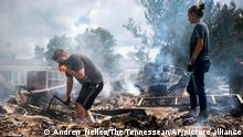 22.08.2021 Josh Whitlock and Stacy Mathieson look through what is left of their home after it burned following flooding in Waverly, Tenn., Sunday, Aug. 22, 2021. Heavy rainfall rapidly turned the creeks that run behind backyards and through downtown Waverly into raging rapids. (Andrew Nelles/The Tennessean via AP)