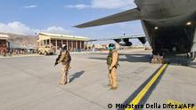 """22.07.2021 This handout picture released and taken by the Italian Defence press office on August 22, 2021 shows soldiers on the tarmac waiting for passengers, who fled Afghanistan, to board on an Italian military aircraft at Kabul airport, to fly to Rome Fiumicino. (Photo by - / MINISTERO DELLA DIFESA / AFP) / RESTRICTED TO EDITORIAL USE - MANDATORY CREDIT AFP PHOTO/ MINISTERO DELLA DIFESA - NO MARKETING - NO ADVERTISING CAMPAIGNS - DISTRIBUTED AS A SERVICE TO CLIENTS / """"The erroneous mention[s] appearing in the metadata of this photo by - has been modified in AFP systems in the following manner: IN CAPTION [Kabul airport] instead of [Kuwait International Airport] and DATELINE and SLUG. Please immediately remove the erroneous mention[s] from all your online services and delete it (them) from your servers. If you have been authorized by AFP to distribute it (them) to third parties, please ensure that the same actions are carried out by them. Failure to promptly comply with these instructions will entail liability on your part for any continued or post notification usage. Therefore we thank you very much for all your attention and prompt action. We are sorry for the inconvenience this notification may cause and remain at your disposal for any further information you may require."""""""