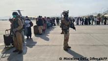 """22.08.2021 This handout picture released and taken by the Italian Defence press office on August 22, 2021 shows soldiers on the tarmac past passengers, who fled Afghanistan, waiting to board on an Italian military aircraft at Kabul airport, to fly to Rome Fiumicino. (Photo by - / MINISTERO DELLA DIFESA / AFP) / RESTRICTED TO EDITORIAL USE - MANDATORY CREDIT AFP PHOTO/ MINISTERO DELLA DIFESA - NO MARKETING - NO ADVERTISING CAMPAIGNS - DISTRIBUTED AS A SERVICE TO CLIENTS / """"The erroneous mention[s] appearing in the metadata of this photo by - has been modified in AFP systems in the following manner: IN CAPTION [Kabul airport] instead of [Kuwait International Airport] and DATELINE and SLUG. Please immediately remove the erroneous mention[s] from all your online services and delete it (them) from your servers. If you have been authorized by AFP to distribute it (them) to third parties, please ensure that the same actions are carried out by them. Failure to promptly comply with these instructions will entail liability on your part for any continued or post notification usage. Therefore we thank you very much for all your attention and prompt action. We are sorry for the inconvenience this notification may cause and remain at your disposal for any further information you may require."""""""