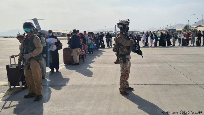 Итальянские военные в Кабуле следят за посадкой пассажиров на эвакуационный рейс в Рим, 22 августа 2021 года