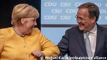Berlin, 21.08.2021, Armin Laschet, Kanzlerkandidat der Union, CDU-Bundesvorsitzender und Ministerpräsident von Nordrhein-Westfalen, steht neben Bundeskanzlerin Angela Merkel (CDU) auf der Bühne am Ende beim zentralen Wahlkampfauftakt von CDU und CSU. Mit der Veranstaltung im Tempodrom will die Union die heisse Phase zum Wahlkampf für die Bundestagswahl 2021 beginnen.