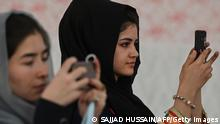 Afghan women use their mobile phones to take pictures of a gathering at a hall in Kabul on August 2, 2021 against the claimed human rights violations on women by the Taliban regime in Afghanistan. (Photo by SAJJAD HUSSAIN / AFP) (Photo by SAJJAD HUSSAIN/AFP via Getty Images)