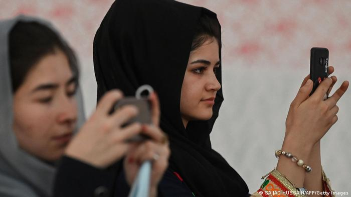 Afghan women use their mobile phones to take pictures of a gathering at a hall in Kabul on August 2, 2021