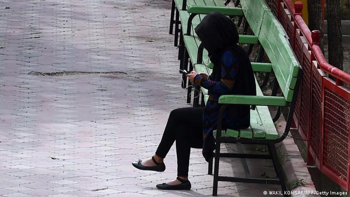 Schwarz gekleidete Frau mit Kopftuch sitzt allein auf einer Bank und schaut auf ihr Handy.