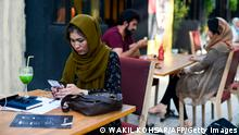 In this picture taken on August 5, 2019, a woman uses her mobile phone in a cafe in Kabul. - The historic deal between the US and the Taliban leaves unresolved the fate of Afghan women, whose fragile gains could come under threat as the brutally repressive insurgents seek to expand their influence. (Photo by Wakil KOHSAR / AFP) / TO GO WITH ' Afghanistan-conflict-peace-Taliban-women, INTERVIEW' by Thomas Watkins (Photo credit should read WAKIL KOHSAR/AFP via Getty Images)