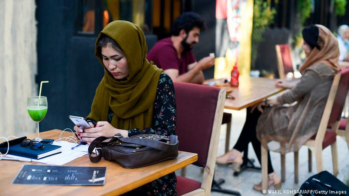A woman looks at her smartphone in a cafe