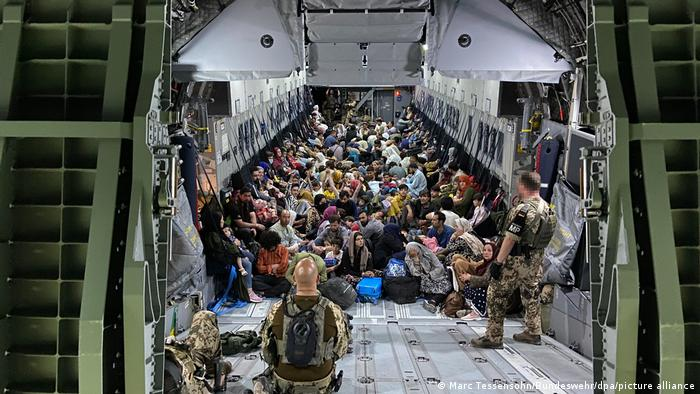 Evacuees pictured in a German transport plane, with flight crew standing nearby
