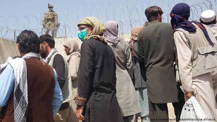 Ludzie czekają przed ogrodzeniem lotniska w Kabulu