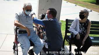 Пожилому мужчине в Калифорнии делают прививку от коронавируса