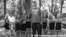 FILE- In this Aug. 15, 2011 photo, Seven-foot, eight-inch tall, Igor Vovkovinskiy, the self proclaimed biggest supporter of President Barack Obama, takes a photo with cheerleaders from the Cannon Falls high school prior to a President Barack Obama town hall event at Lower Hannah's Bend Park, in Cannon Falls, Minn. Vovkovinskiy, the tallest man in the United States, has died in Minnesota. He was 38. His family says the Ukrainian-born Vovkovinskiy died of heart disease Friday, Aug. 20, 2021, at the Mayo Clinic in Rochester. (AP Photo/Nati Harnik/file)