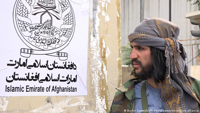 A Taliban fighter in Kabul on August 17, 2021 next to a poster proclaiming the 'Islamic Emirate of Afghanistan'