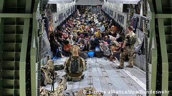 Des réfugiés afghans évacués dans un avion de l'armée allemande.