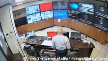 In this undated frame grab taken from video shared with The Associated Press by a self-identified hacker group called The Justice of Ali, a guard looks at surveillance screens taken over by the group, at Evin prison in Tehran, Iran. The alleged hackers said the release of the footage was an effort to show the grim conditions at the prison, known for holding political prisoners and those with ties abroad who are often used as bargaining chips in negotiations with the West. The caption on the screens reads in Farsi: Cyberattack: Evin prison is a stain on (Iranian President Ebrahim) Raisi's black turban and white beard. General protest until the freedom of political prisoners. (The Justice of Ali via AP)