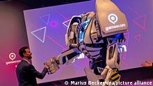 Köln, 23.08.2021 - Felix Falk, Geschäftsführer des Branchenverbands game, begrüßt nach einer Pressekonferenz den Gamesbot, das Maskottchen der Gamescom. Am 25.8. wird die Spielemesse Gamescom eröffnet - allerdings nicht wie sonst in den Kölner Messehallen, sondern pandemiebedingt und wie schon 2020 als rein digitale Veranstaltung. +++ dpa-Bildfunk +++