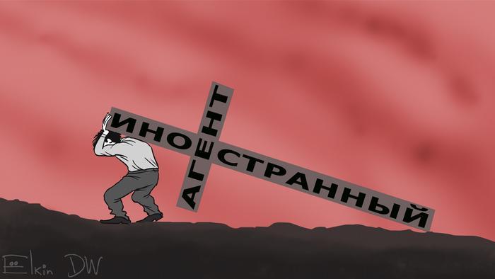 Человек несет крест, на котором написано иностранный агент