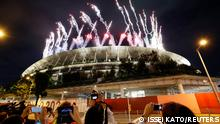 Tokyo 2020 Paralympic Games - The Tokyo 2020 Paralympic Games Opening Ceremony - Olympic Stadium, Tokyo, Japan - August 24, 2021. People take pictures of fireworks during the opening ceremony from outside the stadium. REUTERS/Issei Kato