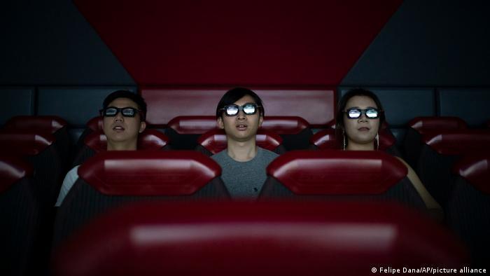 Drei Menschen sitzen mit 3-D-Brillen im Kino.