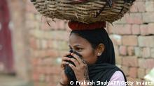 TO GO WITH AFP STORY INDIA-HEALTH-POVERTY-SEWAGE-SCAVENGERS by Adam Plowright In this picture taken on August 10, 2012, a manual scavenger covers her nose while carrying human waste on her head after cleaning the dry toilets in Nekpur village, Muradnagar in Uttar Pradesh, some 40 kms east of New Delhi. Already illegal under a largely ineffective 1993 law, the government has promised to have another go at stamping out the practice with new legislation set to come up in the last parliament session of the year, which opens this week. AFP PHOTO/ Prakash SINGH (Photo credit should read PRAKASH SINGH/AFP via Getty Images)