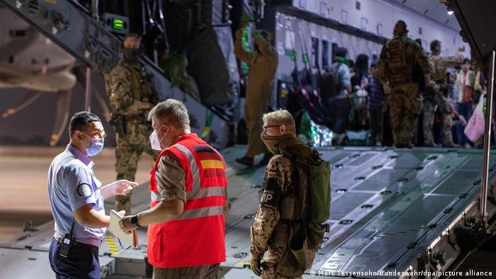 Des représentants de l'Allemagne et de l'Ouzbekistan comparent les listes des passagers évacués d'Afghanistan vers Tachkent