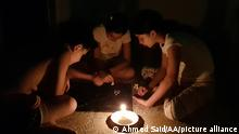 TRIPOLI, LEBANON - AUGUST 23: Kids play a game by candle light due to power cut amidst a deepening economic crisis sparking various shortages of basic staples in the country in Tripoli, Lebanon on August 23, 2021. The fuel crisis in Lebanon started on August 11, when the central bank decided to stop importing fuel on the exchange rate of 3,900 liras to dollar. The crisis led to prolonged power cuts on residential areas, adding more burdens on the Lebanese people. Ahmed Said / Anadolu Agency
