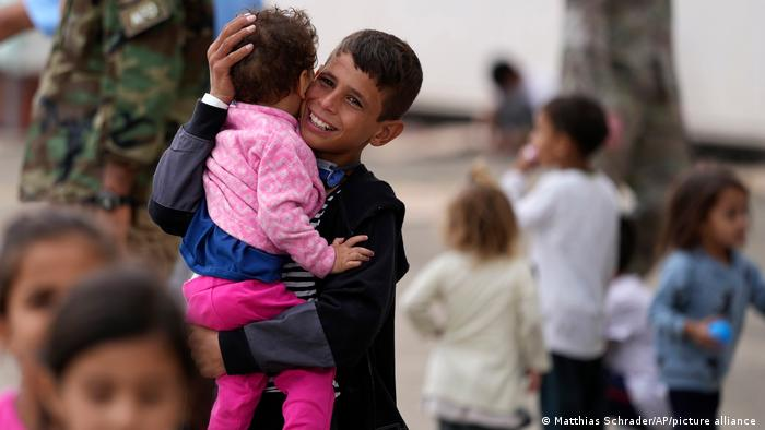 An evacuated young Afghan boy carries a child at the Ramstein US Air Base, Germany