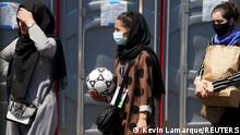 An Afghan woman holding a soccer ball and wearing a CAFA (Central Asian Football Association) credential, waits in line at a processing center for refugees evacuated from Afghanistan at the Dulles Expo Center near Dulles International Airport in Chantilly, Virginia, U.S., August 24, 2021. REUTERS/Kevin Lamarque