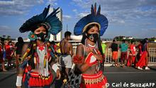 Indigenous women from the Krenak tribe are seen during a protest outside the Supreme Court Building in Brasilia, on August 24, 2021. - Over 1000 indigenous protestors have converged on Brasilia to take part in a week of protests organised by Articulacao dos Povos IndÌgenas do Brasil (Apib). The main focus of the protests is a forthcoming judgment at the Supreme Court (STF) on August 25, 2021 which may define the future demarcation of Indigenous Lands. (Photo by CARL DE SOUZA / AFP)