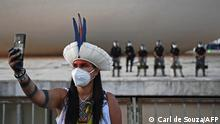 An indigenous woman takes a selfie in front of riot police during a protest outside the Supreme Court building in Brasilia, on August 24, 2021. - Over 1000 indigenous protestors have converged on Brasilia to take part in a week of protests organised by Articulacao dos Povos IndÌgenas do Brasil (Apib). The main focus of the protests is a forthcoming judgment at the Supreme Court (STF) on August 25, 2021 which may define the future demarcation of Indigenous Lands. (Photo by CARL DE SOUZA / AFP)