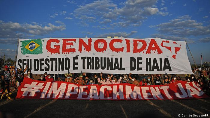 Indigenous protestors hold a banner that reads Genocides, your fate is the Hague court during a protest outside the Supreme Court building in Brasilia, on August 24, 2021.