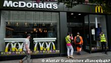 Customers walks into a branch of a McDonald's restaurant, in London, Tuesday, Aug. 24, 2021. McDonald's says it has pulled milkshakes from the menu in all 1,250 of its British restaurants because of supply problems stemming from a shortage of truck drivers. The fast-food chain says it is also experiencing shortages of bottled drinks. (AP Photo/Alastair Grant)