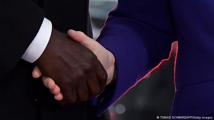 Handshake between AU Commission Chariman Moussa Faki and Angela Merkel in 2019