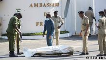 Tanzanian security forces prepare to remove the slain body of an attacker who was wielding an assault rifle, outside the French embassy in the Salenda area of Dar es Salaam, Tanzania August 25, 2021. REUTERS/Emmanuel Herman NO RESALES. NO ARCHIVES
