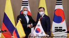 South Korean President Moon Jae-in, right, shakes hands with his Colombian counterpart Ivan Duque prior to a meeting at the presidential Blue House in Seoul, South Korea, Wednesday, Aug. 25, 2021. Duque arrived on Tuesday for a three-day to strengthen cooperation between the two countries in the digital, environmental and cultural fields. (Choe Jae-koo/Yonhap via AP)