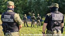 PODLASIE VOIVODESHIP, POLAND - AUGUST 20, 2021: Armed Polish soldiers (front and midground) and Afghan refugees (back) who have fled the Taliban are seen near the village of Usnarz Gorny in eastern Poland on the border to Belarus. A group of 30 refugees have been stranded at the Polish-Belarusian border under the custody of Polish law enforcement officers for 12 days after illegally crossing the border. Armed members of Belarusian security forces do not let them return to Belarus while Polish border guards and army officers prevent them from continuing their journey across Poland. Irina Polina/TASS