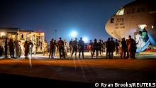 Afghan evacuees leave a U.S. C-17 Globemaster after arriving to Ali Al Salem Air Base, Kuwait, August 24, 2021. Picture taken August 24, 2021. U.S. Air Force/Staff Sgt. Ryan Brooks/Handout via REUTERS THIS IMAGE HAS BEEN SUPPLIED BY A THIRD PARTY.