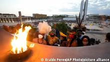 Indigenous people stand near the Pyre of freedom during the Luta pela Vida, or Struggle for Life mobilization, a protest to pressure Supreme Court justices who are expected to issue a ruling that will have far-reaching implications for tribal land rights, at Praca dos Tres Poderes or Three Powers Plaza, in Brasilia, Brazil, Wednesday, Aug. 25, 2021. (AP Photo/Eraldo Peres)