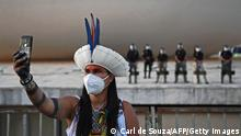 An indigenous woman takes a selfie in front of riot police during a protest outside the Supreme Court building in Brasilia, on August 24, 2021. - Over 1000 indigenous protestors have converged on Brasilia to take part in a week of protests organised by Articulacao dos Povos Indígenas do Brasil (Apib). The main focus of the protests is a forthcoming judgment at the Supreme Court (STF) on August 25, 2021 which may define the future demarcation of Indigenous Lands. (Photo by CARL DE SOUZA / AFP) (Photo by CARL DE SOUZA/AFP via Getty Images)