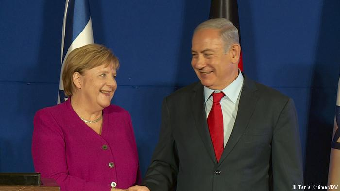 A woman and a man shake hands in front of a blue backdrop.